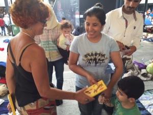 Expressão facial de uma mãe refugiada vendo seu filho receber um pacote de biscoito.