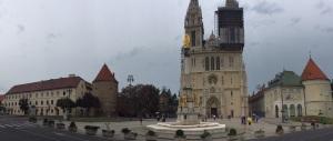 Panorâmica da Praça Kaptol, onde está a Catedral de Assunção da Sagrada Virgem Maria , a escultura de Nossa Senhora e circundando a igreja, está o Palácio do Arcebispo - Zagreb